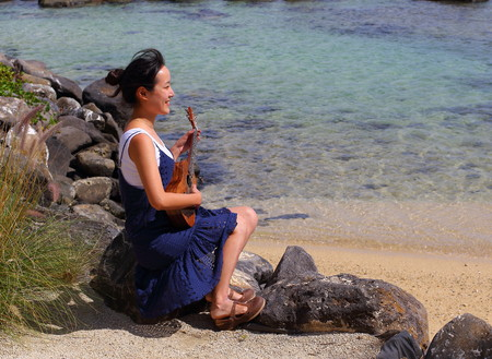 Turtle Bay, Mauritius - an unidentified young woman sits on a rock next to the sea playing a small guitar in landscape format with copy space