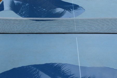 Abstract of a wet blue outdoor table tennis table with large water puddles on from rain in landscape format with copy space