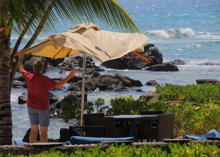 Balaclava, Mauritius - unidentified guest puts up a beach umbrella in the sea breeze at the Westin Turtle Bay Resort and Spa on the island