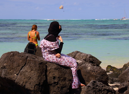 bather: Ile aux Cerfs, Mauritius - unidentified young woman in traditional Muslim dress looks out over the ocean as another unidentified bather in a bikini stands nearby