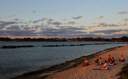 Turtle Bay, Mauritius - unidentified persons do yoga on the beach at sunset in landscape format with copy space