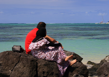 Ile aux Cerfs, Mauritius - unidentified Muslim couple relax on the beach on the tropical Indian Ocean island in landscape format with copy space