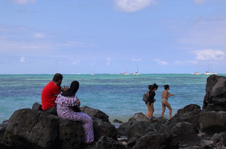 Ile aux Cerfs, Mauritius - unidentified Muslim couple look on as unidentified holidaymakers dressed in swimwear walk on the beach
