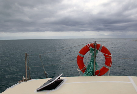 View of the open ocean from the deck of a yacht on a blustery cloudy day in landscape format with copy space