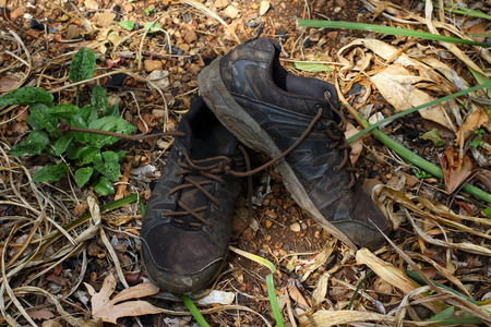 Pair of dirty old black shoes abandoned outdoors in landscape format Stok Fotoğraf