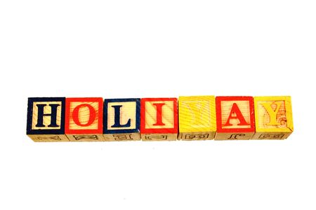 The term holiyay visually displayed on a white background using colorful wooden toy blocks in landscape format with copy space