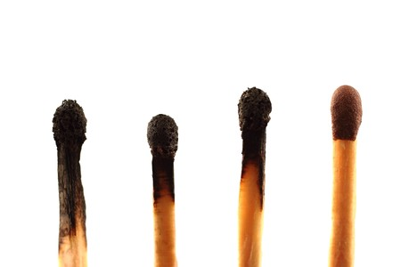 expired: Four matches - three used and one unused - against a white background in landscape format with copy space Stock Photo