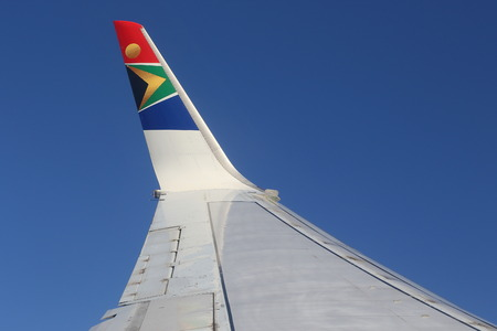 Johannesburg, South Africa - the wing of a South African Airways aircraft against a clear blue sky background in landscape format with copy space