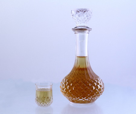 Crystal decanter and a small glass filled with a golden liquid on a white background image in landscape format with copy space
