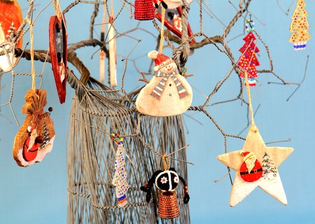 Authentic African wire art Christmas tree decorated with handmade trimmings image against a clear blue background in landscape format with copy space 스톡 콘텐츠