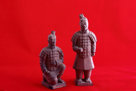 Two model terracotta warriors against a red background image in landscape format with copy space
