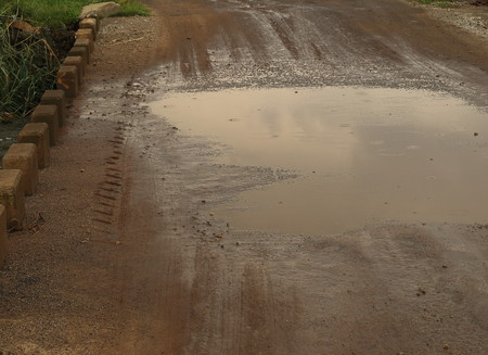 A muddy puddle on a low water bridge on a dirt road on a rainy day image in landscape format