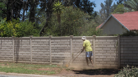 Johannesburg, South Africa - an unidentified homeowner mows what is left of his lawn in severe drought and heat conditions in the country