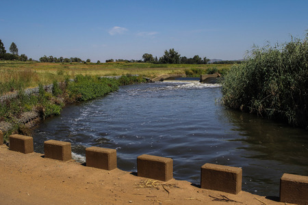African landscape with a low-water bridge, a river and a weir with a clear blue sky, image in landscape format with copy space