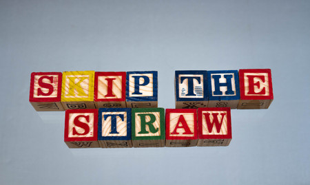 The phrase skip the straw displayed visually on a light background using colorful wooden toy blocks, image in landscape format with copy space