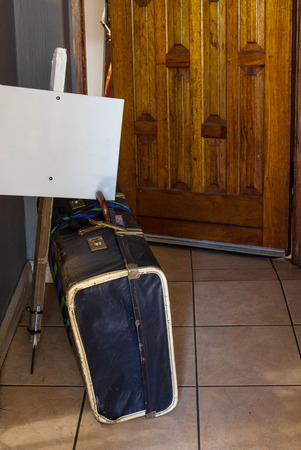 Warn, retro old cardboard suitcase and a blank white placard outside an open doorway Foto de archivo