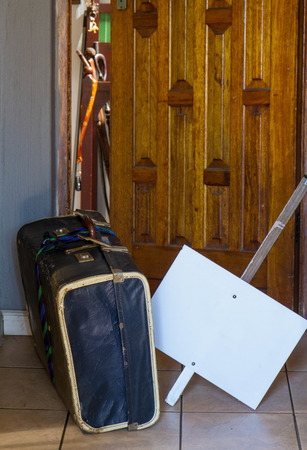 Warn, retro old cardboard suitcase and a blank white placard outside an open doorway 写真素材