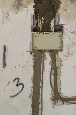 Chases cut into a wall for electrical wiring and plastered over on a building construction site image in portrait format with copy space
