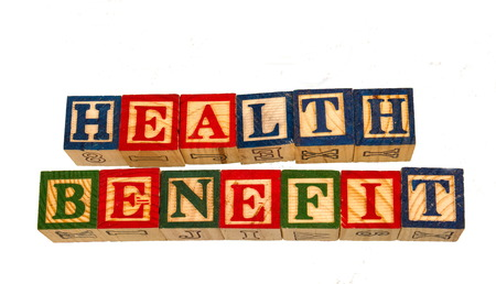The term health benefit visually displayed on a white background using colorful wooden toy blocks image in landscape format Stock Photo