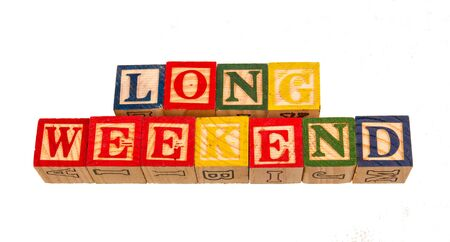 The term long weekend displayed visually on a white background using colorful wooden toy blocks image with copy space in landscape format