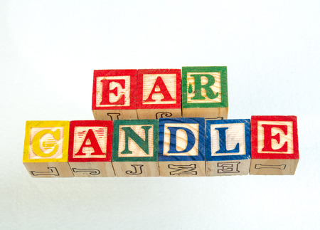 The phrase ear candle visually displayed on a white background using colorful wooden blocks image with copy space in landscape format Stockfoto