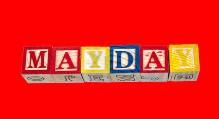 The phrase Mayday visually displayed on a red background using colorful wooden blocks image with copy space in landscape format Stockfoto