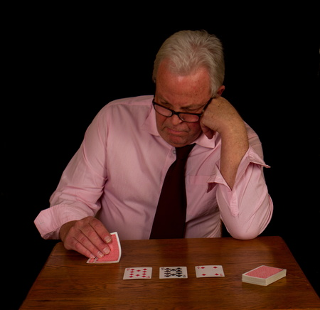 Elderly man with grey hair looking unhappily at his poker hand image with copy space against a black background