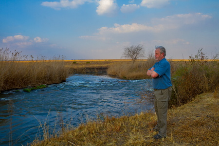 Stern elderly man with grey hair and folded arms looks out over a river on his farm image in landscape format with copy space