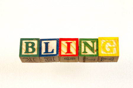 The term bling visually displayed on a white background using colorful wooden toy blocks image with copy space in landscape format