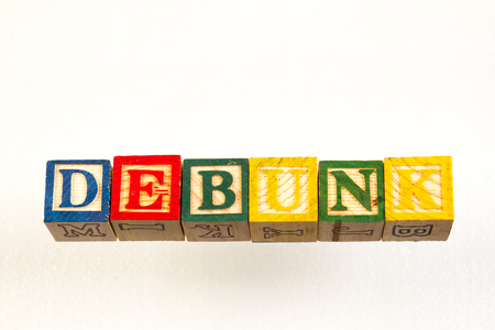 The term debunk visually displayed on a white background using colorful wooden toy blocks image with copy space in landscape format Banque d'images
