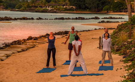 Balaclava, Mauritius - unidentified adults take part in a yoga cession on the beach at sunset image with copy space in landscape format
