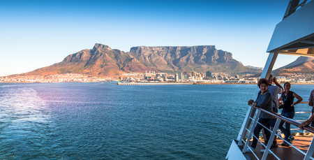 Cape Town, South Africa - unidentified passengers watch excitedly from deck as the liner leaves Table Bay Harbor image with copy space in landscape format