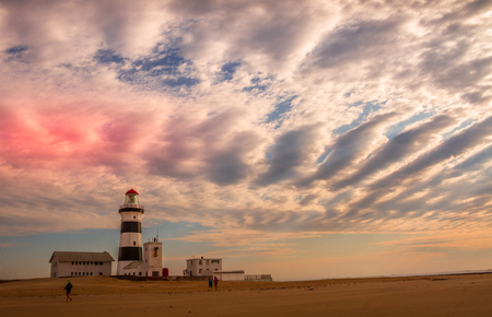 Port Elizabeth, South Africa - unidentified tourists walk on the beach at the landmark Cape Recife Lighthouse image with copy space in landscape format