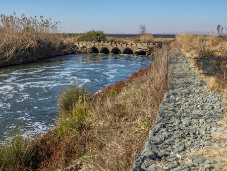 Old concrete low water bridge with a modern gabion retaining wall to control erosion image with copy space in landscape format Stock Photo