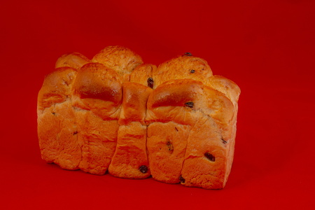 Mosbolletjies is a traditional Afrikaans sweet-bun made in the wine producing areas of the Western Cape province of South Africa isolated on a red background image with copy space in landscape format