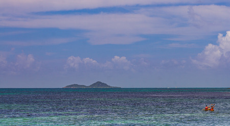 Praslin Island, Seychelles - unidentified holiday-makers paddle offshore in the Indian Ocean image with copy space in landscape format Imagens