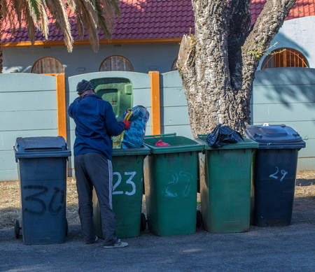 Johannesburg, South Africa - an unidentified unemployed man searches through residential refuse bins image with copy space in landscape format