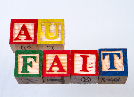 The term au fait displayed visually on a white background using colorful wooden toy blocks