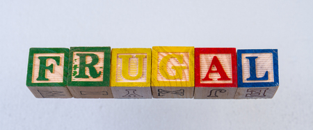 The term frugal displayed visually on a white background using colorful wooden toy blocks Reklamní fotografie