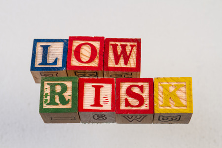 The term low risk displayed visually on a white background using colorful wooden toy blocks