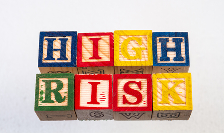 The term high risk displayed visually on a white background using colorful wooden toy blocks