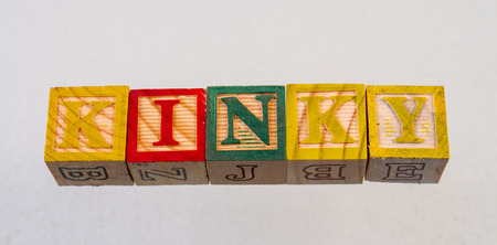 The term kinky displayed visually on a white background using colorful wooden toy blocks
