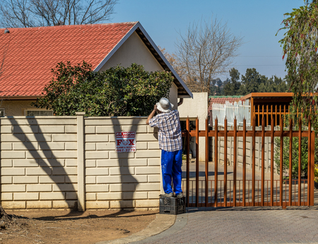 Johannesburg, South Africa - an unidentified caucasian male adult doing some upkeep work on his home