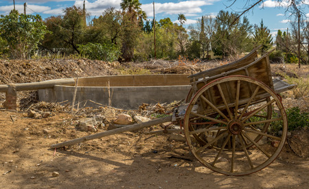 Weathered vintage wooden wagon exposed to the elements in a farmyard