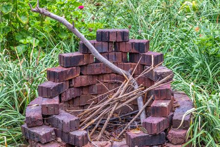 Circular firepit built from loose bricks in a garden setting image in horizontal format