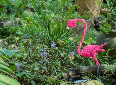 Fake pink flamingo stands isolated in a small garden pond image in horizontal format