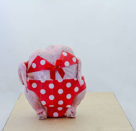 A fresh raw skinned chicken dressed in a red polka dot bikini isolated on a clear background