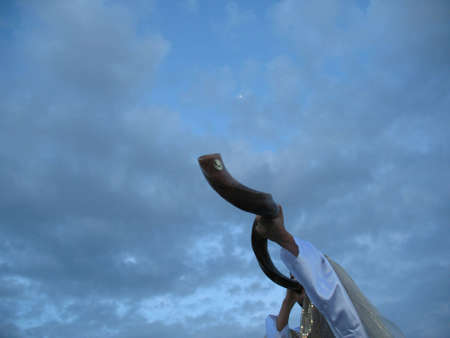 A shofar blower dressed in white and gold blowing the shofar against a blue sun set sky