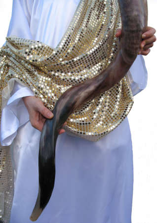 A shofar blower dressed in white and gold