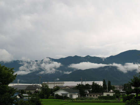 A sleepy Japanese village surrounded by mountains and clouds